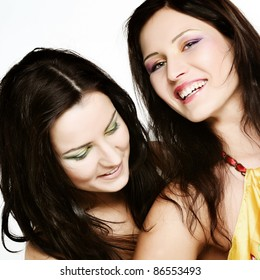 Two girl friends together smiling.Studio shot.