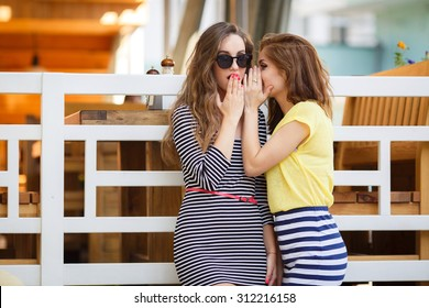 Two girl friends whispering secrets. summer holidays and vacation concept - girls gossiping . friendship, gossip and happiness concept - one girl telling another secret