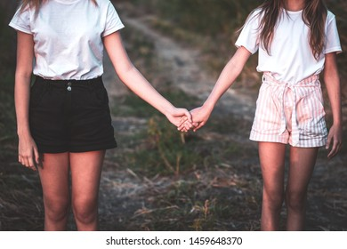 Two girl holding hand and walking on the road. Young women couple on the beautiful landscape.