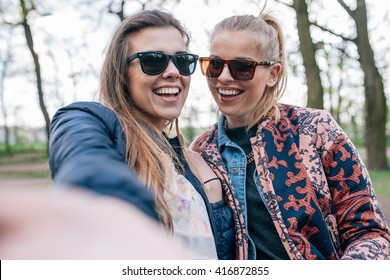 Two girl sitting on the bech in the park and taking selfie