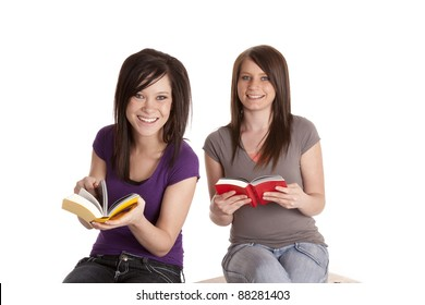Two girl sitting and reading books on a bench.