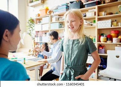 Two girl standing in classroom and having nice conversation while attending art school together