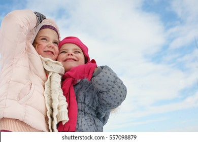 Two girl standing and looking something in the sky. Space for copy.