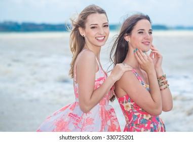 Two girlfriend walking on summer the beach