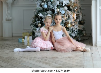 Two girlfriends of the ballerina in a pink dress the Christmas tree