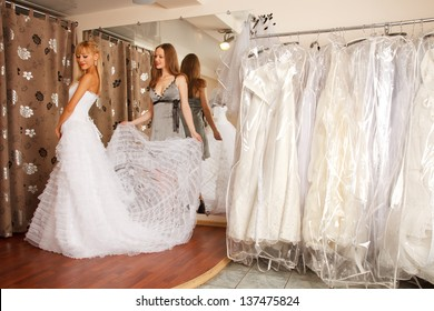 Two girlfriends  - A Bride-To-Be and  bridesmaid  - having fun -Trying On A Wedding Dress