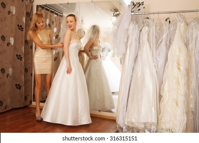 Two girlfriends - A Bride-To-Be and bridesmaid Trying On A Wedding dress