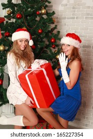 Two girlfriends with a gift near the Christmas tree