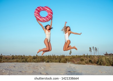 Two girlfriends girl bathing suits, jump with inflatable circle, holiday birthday party nature, white sand summer beach, lifestyle fashion modern trend, tanned fitness figure weekend holiday resort.