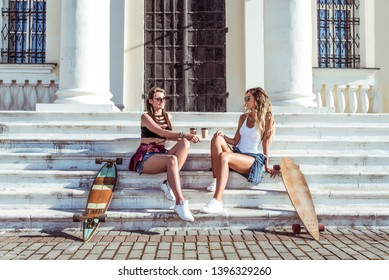 Two girlfriends girls, women sisters, talking steps summer city, skate board, cups coffee, tea. Concept holiday weekend, happy embrace. Fashion style, modern lifestyle. Free space.