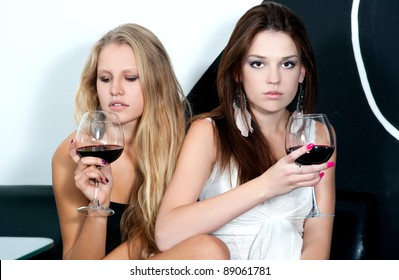 Two girlfriends with two glasses of wine