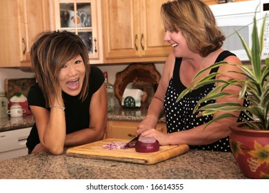 Two Girlfriends Gossiping in the Kitchen While They Cook