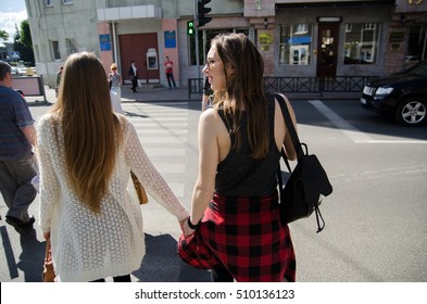 Two girlfriends are having fun walking in the city