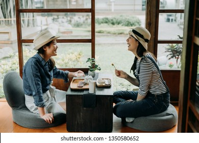 two girlfriends laughing with jokes drinking matcha in tea bowl having culture experience tea ceremony chado. young asian women sit indoor japanese style house by spring garden travel in kyoto japan