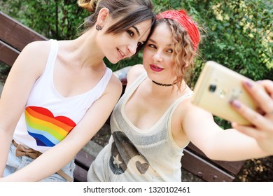 two girlfriends lesbian relieve themselves on camera phones or taking selfies and smiling. LGBT concept, sexual minorities, same-sex couples.
