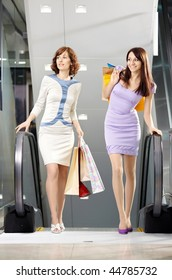 Two girl-friends on shopping has risen on the escalator with bags