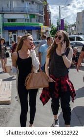 Two girlfriends are playing with the cellphone on the street