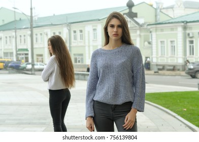 Two girlfriends quarreled, they stand at a distance and do not look at each other. They have long brown hair and clean beautiful skin