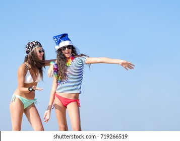 Two girlfriends in a Santa hat and in the image of a pirate during a beach holiday. Girl points to the sky.