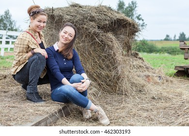 Two girlfriends sitting beside a stack of hay, copyspace