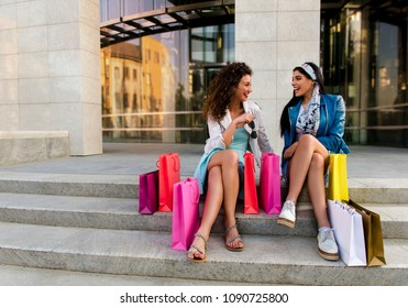 Two girlfriends sitting on stairs with shopping bags and talking in front of  mall