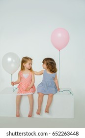 Two girlfriends are sitting on a white box, holding balloons in their hands. Girl stroking girlfriend's hair, curiously studying hairstyle