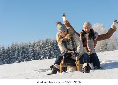 Two girlfriends sledge downhill in sunny wintertime snow wooden sledge
