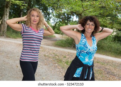 Two girlfriends stretching in sunny park