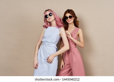 two girlfriends in sunglasses on a beige background