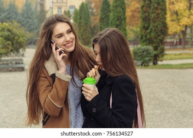 Two girlfriends try to warm up with a hot drink in the outdoors. They are having fun and fooling around, talking on the smartphone and sharing events with each other