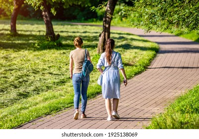 Two girlfriends walk along a path in the Park
