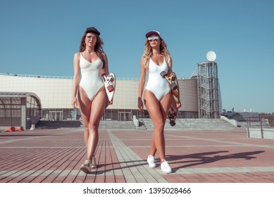 Two girlfriends woman white bathing suit baud, summer city goes on street. Longboard skateboard sunglasses. The girls walking. Concept style fashion lifestyle young people. Long hair tanned figure.