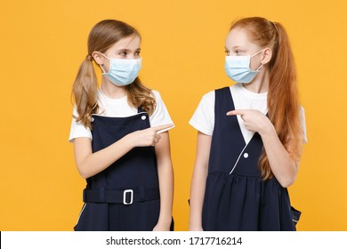 Two girls 12-13 years old in white t-shirt school uniform dresses sterile face mask isolated on yellow background children studio portrait Childhood kids education covid-19 concept Mock up copy space.