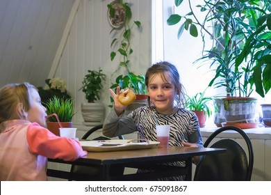 Two girls 7 and 4 years old eating donuts in   cafe.