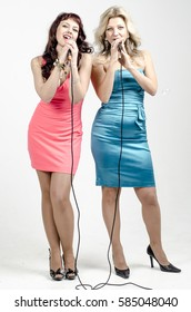 Two Girls actress singer in cocktail dresses with microphones blonde and brown hair