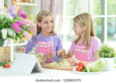 Two girls in aprons preparing fresh salad