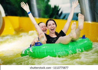 Two girls in an aquapark on a rubber ring laughing happily skate on water slides splashing water and sun