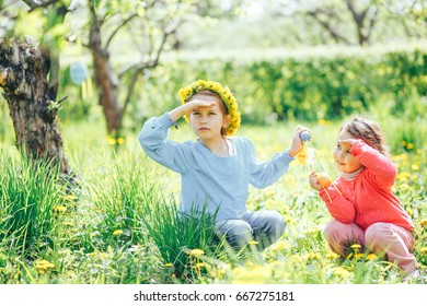 Two girls of Asian and Caucasian appearance, collect Easter eggs in the lush garden