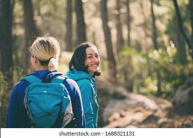 バックパックを持つ2人の女の子が森を歩く。山の中をハイキング。彼女は自然の中で一緒に時間を過ごす。女は公園を歩く。