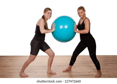 Two girls balancing a blue exercise ball