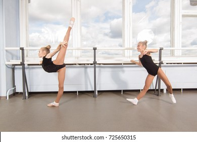 Two girls ballerinas perform exercises in the classroom for choreography classes