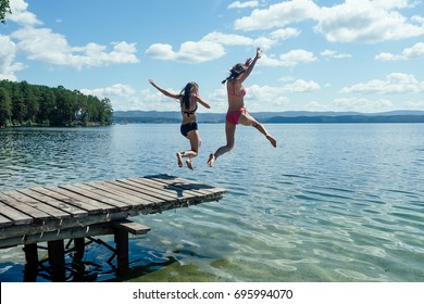 Two girls in bathing suits jumping from a wooden pier into the water against a background of blue mountains in the sunlight