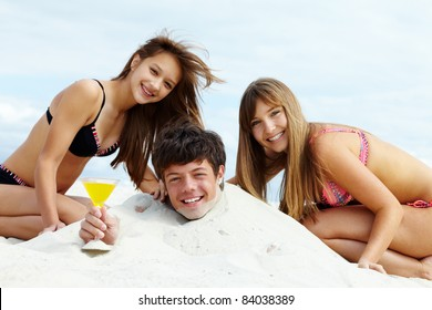 Two girls in bikini and happy guy with cocktail having fun on sandy beach
