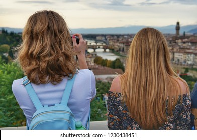 Two girls blondes look at the panorama of Florence. One of the girls with straight hair, the other - with curls. Curly girl takes pictures.