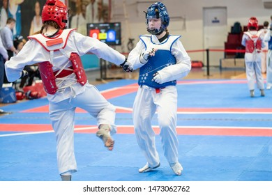 two girls in blue and red Taekwondo equipment are fighting at doyang