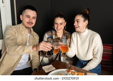 two girls and a boy clink their glasses in a toast.