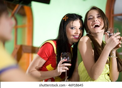 Two girls and boy are drinking wine together