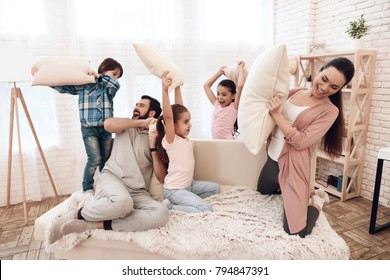 Two girls and a boy fight with pillows with their parents. They have fun in their apartment.