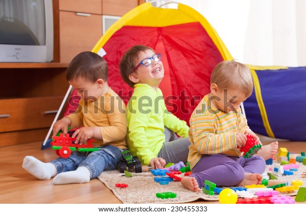Two girls and boy with toys on  floor at home.