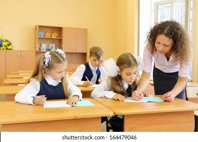 Two girls and boy write at school desks in classroom and teacher helps at school.
